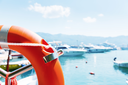 Lifebuoy in sea port against yachts at summer day