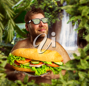 Happy man in glasses with a big sandwich against nature