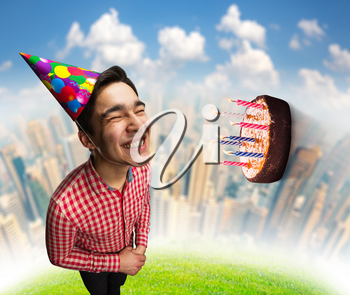 Happy smiling birthday boy with cake flying to his face