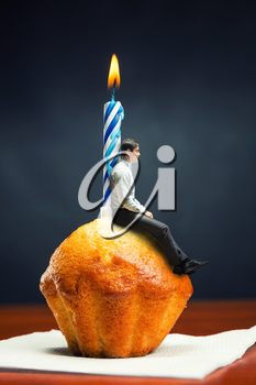 Sad birthday boy sits on cake with candle on the table