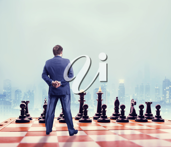 Businessman standing in front of the black team on the chess board