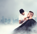 Young man having his beard shaven, barber working with comb over dark city background