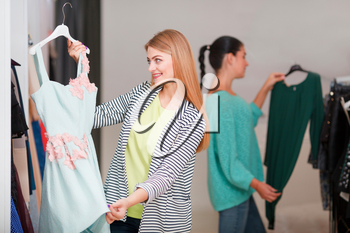Two women shopping, one is excited holding a cute dress