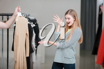 Excited woman looking at the dress prepared by shop assistant