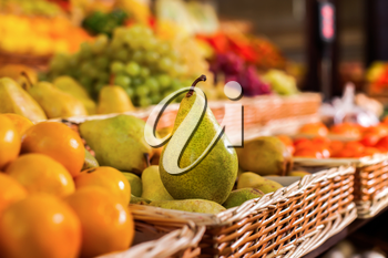 Ripe pear in front of boxes with fresh fruits and vegetables against the background of a market.. Ecological food. Healthy lifestyle.