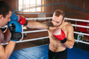 Boxer sents his opponent to the knockout. Fighting ring on the background. Box sport.
