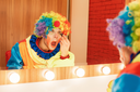 Cheerful clown does a make-up in front of the mirror. Makeup room at the background