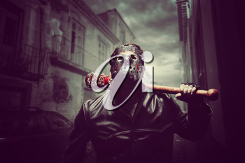 Angry psycho man in hockey mask and black leather coat with bloody baseball bat with a chain wrapped around. Maniac waiting for his victim on night city street