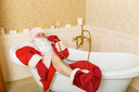 Funny drunk Father Christmas lies in a bath and talking by shower.