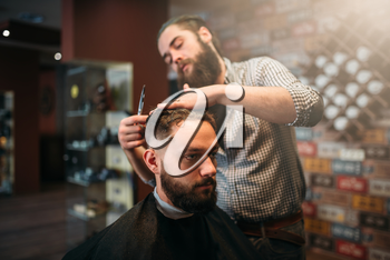 Coiffeur cutting by scissors hair of the customer man in black salon cape, barbershop on background