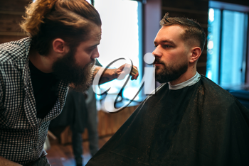 Barber styling mustache and beard at the barbershop. Hairdressing concept