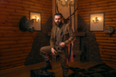 Respectable hunter man with old gun in retrro style traditional hunting clothing standing against antique chest. Retro rifle, vintage clothes. Room with fireplace, stuffed wild animals, bear skin and