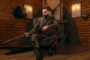 Hunter man in vintage hunting clothing sitting in a chair with antique rifle. Fireplace, stuffed wild animals, bear skin and other trophies on background. Hunt lifestyle