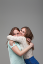 Two happy girlfriends hugs together, studio photo shoot. Female friendship