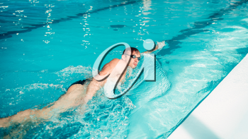 Athletic swimmer in glasses swims in butterfly style, indoor swimming pool