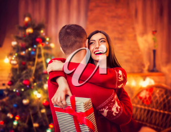 Happy love couple hugs, christmas holidays. Xmas celebration, cheerful man and woman with gift, fir-tree with decoration on background