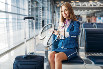 Stewardess with suitcase sitting on seat in waiting area in airport and looks at clocks. Air hostess with baggage, flight attendant with hand luggage, aviatransportations job