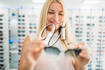 Female optician shows sunglasses in optics store. Selection of eyes protection with professional optometrist, optometry concept