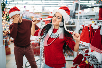 Funny young couple trying on christmas clothes in supermarket, family tradition. December shopping of holiday goods and decorations