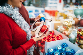 Female person buying christmas tree balls in supermarket, family tradition. December shopping of holiday goods