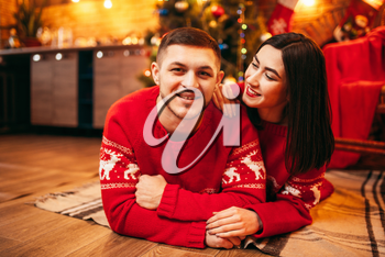 Happy love couple lies on the floor, christmas holidays. Xmas celebration, cheerful man and woman in red pullovers, fir-tree with decoration on background