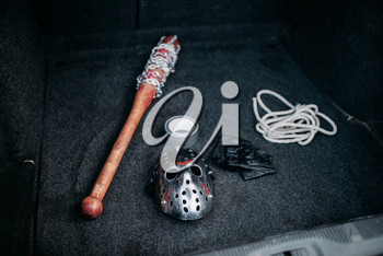 Psycho man instruments in opened car trunk, maniac. Hockey mask, baseball bat wrapped with bloody metal chain, leather fingerless gloves, duct tape and rope, serial murderer collection
