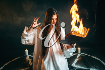 Young woman in white shirt sitting in the center of burning pentagram circle and reads spellbook, gark magic ritual