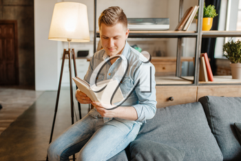 Young man sitting in couch and reading a book. Male person reads in living room, floor lamp and shelf on background