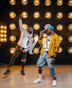 Two black rappers in caps, dance perfomance in club, stage with spotlights on background. Rap performers on scene with lights, underground music concert, urban style