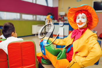 Funny clown animator and group of little boys. Birthday celebrating in playroom, baby holiday in playground. Childhood happiness, childish leisure, entertainment in children's area
