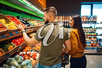 Couple with basket in grocery supermarket together. Man and woman buying fruits and vegetables in market, customers shopping food