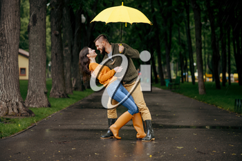Happy love couple dancing in park in summer rainy day. Man and woman hugs under umbrella in rain, romantic date on walking path, wet weather in alley