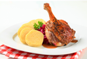 Dish of roast duck leg with potato dumplings and red cabbage