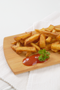 heap of fried chipped potatoes with ketchup on wooden cutting board