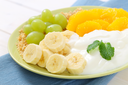 plate of muesli with white yogurt and fresh fruit on blue place mat - close up