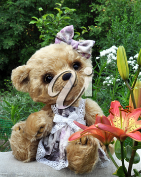 Handmade, the sewed toy: teddy-bear Lucky on a on an ancient linen cloth among flowers