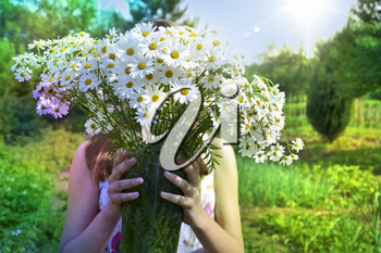 girl with a bouquet of white field chamomiles on a summer sunny day