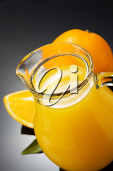 orange juice and fruit on black background
