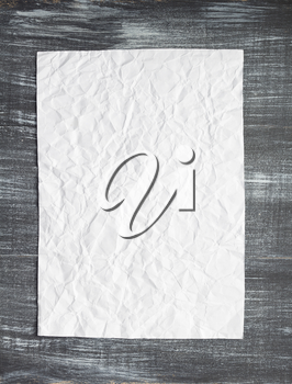 empty white wrinkled paper at wooden background