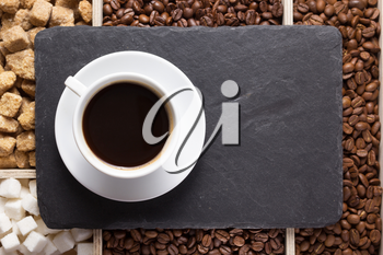 cup of coffee and beans on slate stone black tray background, top view