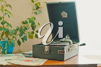 The ancient record player plays music from a vinyl record.