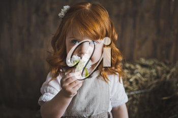 Portrait of a red-haired child with a white flower.