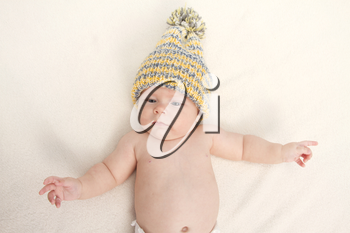 baby in a hat on the bed