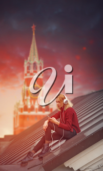 girl listening to music on the roof on the background of the Red Square in Moscow