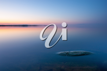 Tranquil minimalist landscape with rock in calm water of lake with smooth surface with horizon with clear blue sky in twilight, simple beautiful calm natural blue background.