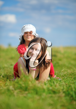 Mother and her little daughter enjoying a sunny summer day lying on green grass. Shallow depth of field. Selective focus on mother's face. Vertical shot.