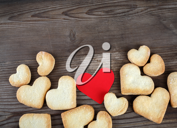 Heart shaped cookies and red heart on wooden background. Top view. Space for text on top.