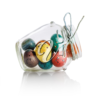 Bright colorful easter eggs in a glass jar. Easter still life. Isolated with clipping path on white background.