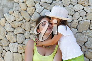 Portrait of mother and daughter. Smiling young woman and child on the background of an old stone wall.