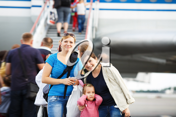 Two young smiling women and child girl posing in the blurry background ladder passenger aircraft at the airport. Passengers on the airliner background. Shallow depth of field. Selective focus.